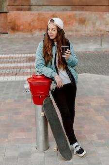 Skateboarder dziewczyna trzyma filiżankę kawy odwracając wzrok