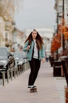 Skateboarder dziewczyna trzyma filiżankę kawy podczas jazdy na deskorolce