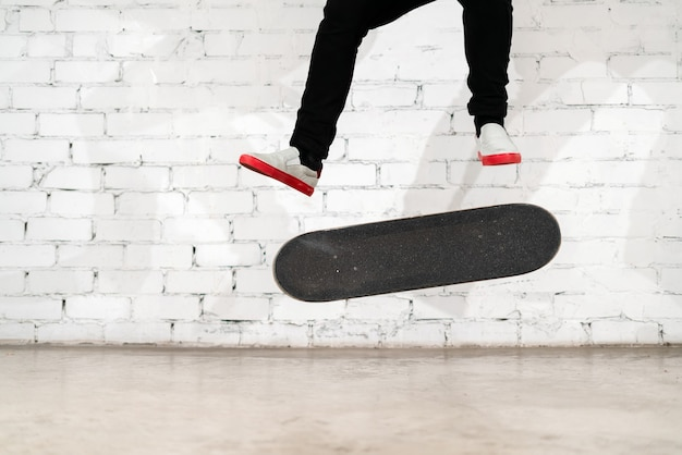 Skateboarder wykonujący trik z deskorolką na betonie.