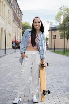 Skater dziewczyna trzymająca deskorolkę pozuje do zdjęć na zewnątrz