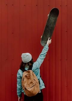 Skater dziewczyna w miejskich gospodarstwa skate w powietrzu