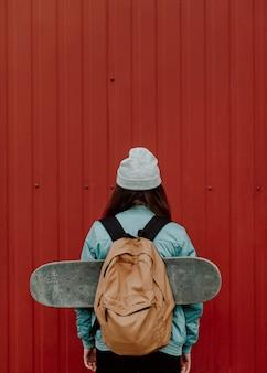 Skater dziewczyna w przestrzeni miejskiej z tyłu strzał kopii przestrzeni