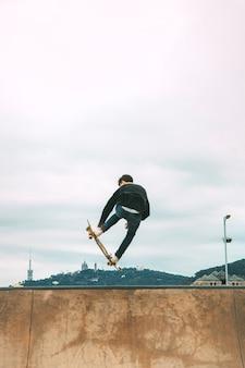 Skater skaczący wysoko w powietrzu z snakeboard w skateparku skopiuj przestrzeń
