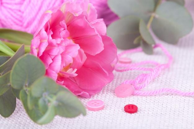 Skein różowy przędzy zbliżenie, guziki, tulipan. wiosenna kompozycja, delikatność, pocztówka