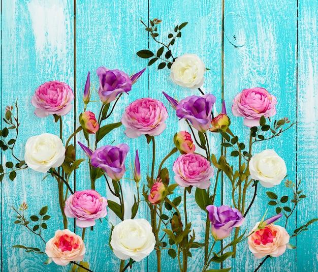 Skład białe, różowe róże, kwiaty i liście na białym tle na drewniane tła. leżał płasko, widok z góry