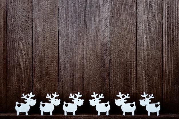 Skład biali renifery na drewnianym tle. świąteczny wystrój