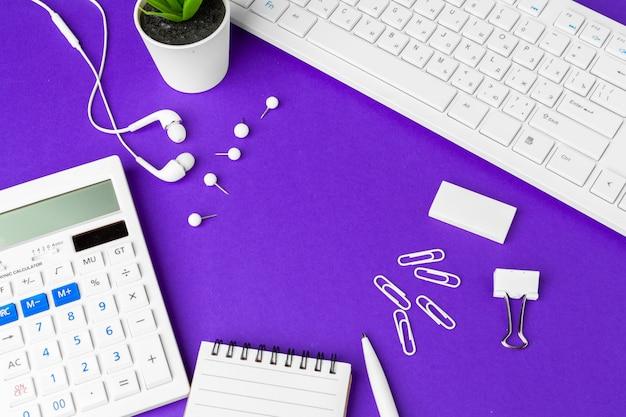 Skład biurowego stylu życia rzeczy na purpurowym tle, klawiatura komputerowa materiały biurowe na biurku w biurze