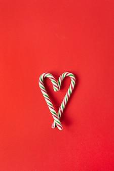 Skład boże narodzenie nowy rok. symbol serca wykonany z trzciny cukrowej laski na czerwono
