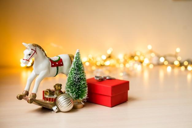 Skład bożego narodzenia i nowego roku. czerwone pudełko ze złotymi złotymi światłami boke, ozdobami świątecznymi. zdjęcie wysokiej jakości