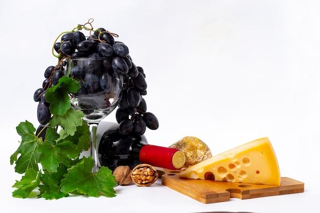 Skład, butelka czerwonego wina, sera i winogron,