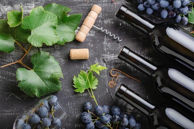 Skład czerwonego wina na stole z czarnej kredy kamiennej. widok z góry. butelki czerwonego wina winogrona, kiście winogron, liście i winorośli korkociąg korki wino na ciemnym tle rustykalnym betonu.