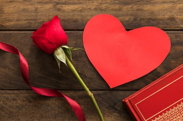 Skład czerwony kwiat blisko faborku i symbolu serce
