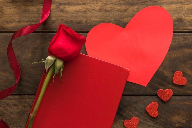 Skład czerwony kwiat blisko faborku, serc i papieru ,.
