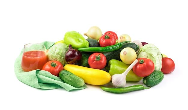 Skład dojrzałych świeżych warzyw i szklankę soku warzywnego z kroplami wody.