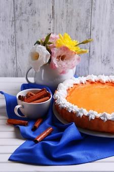 Skład domowej roboty ciasto z dyni na talerzu i kwiaty w wazonie na drewnianej przestrzeni