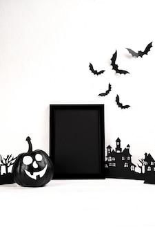 Skład halloween. czarna ramka na zdjęcia i sztuka papieru opuszczona wioska, dynia na białym tle.