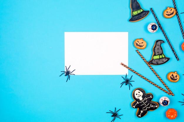 Skład halloween party na niebieskim tle papieru. flat lay, halloween party decor - pierniki, słomki do napojów, dynie, nietoperze i pająki. makieta, kartka z życzeniami, płasko świecki, widok z góry.