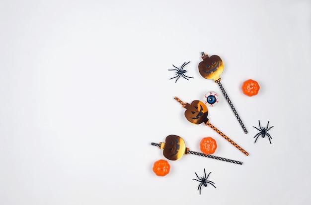 Skład halloween party na tle papieru w kolorze czarnym, pomarańczowym i białym. mieszkanie świecące, wystrój na halloween - słomki do napojów, dynie, nietoperze i pająki. makieta, kartka z życzeniami, płasko świecki, widok z góry.