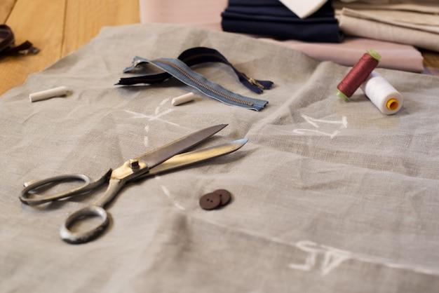 Skład igły i nici z innymi narzędziami krawieckimi. szpula nici, nożyczki, guziki, materiały do szycia. zbliżenie nożyczek, guzików, nici i naparstka na tkaninach.