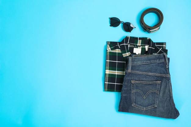 Skład leżał płasko z koszula, dżinsy, okulary i pasek na kolor tła