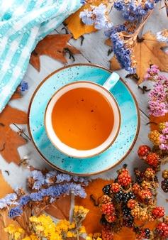 Skład martwa natura z kubkiem gorącej herbaty liściastej z jagodami i jesiennych liści na drewnianej powierzchni