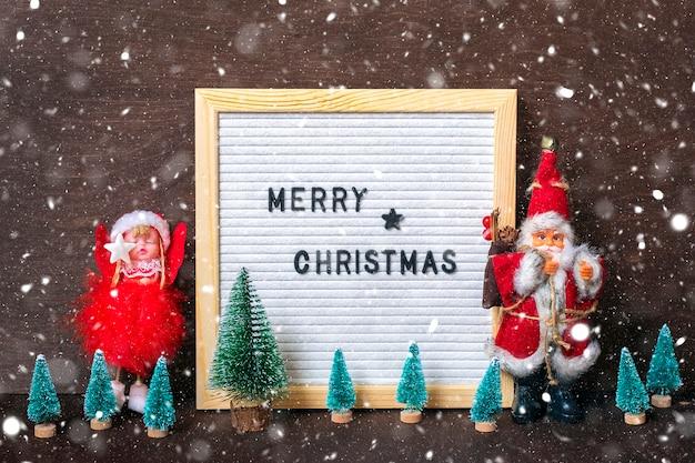 Skład mikołaj, anioł, drzewo, filcowa tablica z tekstem wesołych świąt na podłoże drewniane