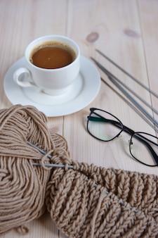 Skład motka przędzy, szklanki, filiżankę kawy na jasnym tle drewniane
