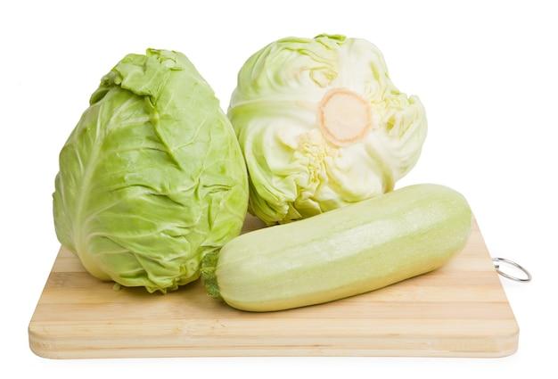 Skład na drewnianym tle organicznej żywności wegetariańskiej: kapusty i cukinii.