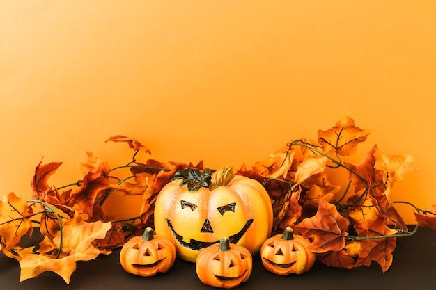 Skład na halloween z liśćmi i uśmiecha się dynie
