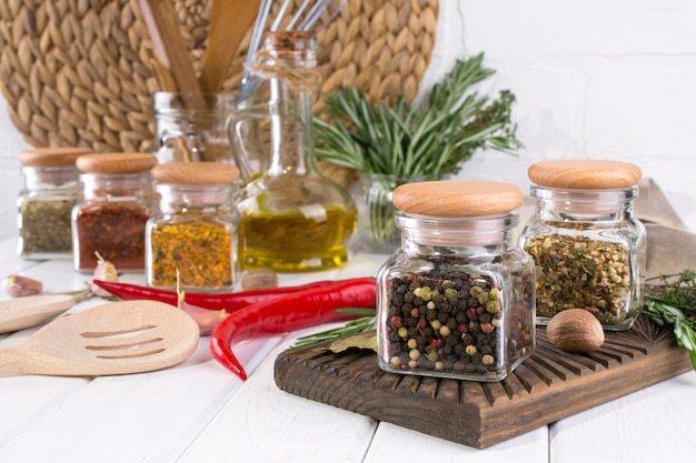 Skład narzędzi kuchennych, przypraw i ziół na białym stole