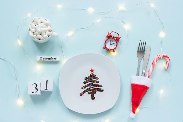 Skład noworoczny kalendarz 31 grudnia. słodka czekoladowa choinka na talerzu, sztućce, kakao, budzik