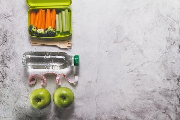 Skład obiad polu zdrowej żywności, butelki wody i jabłek