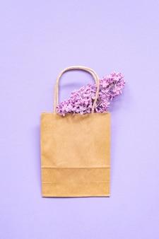 Skład papierowej torby eco z fioletowymi kwiatami bzu. flat lay. widok z góry. koncepcja kreatywna lato.