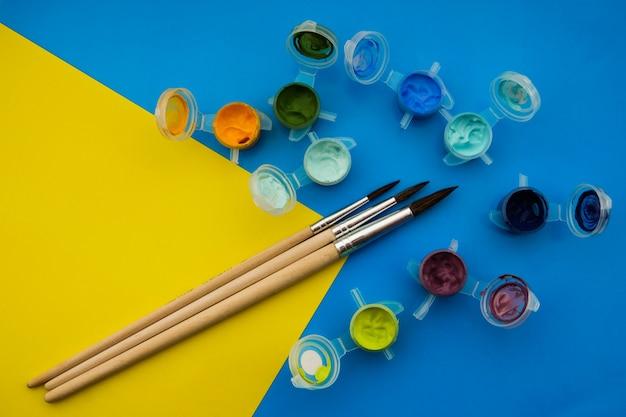 Skład płaski świeckich z różnych farb akrylowych lub olejnych i pędzle na tle grunge.