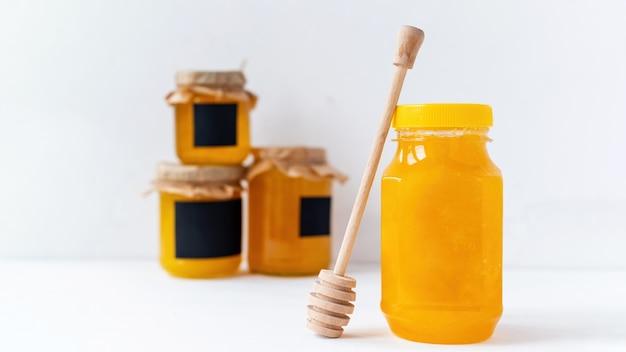 Skład produktów miodowych. miód w słoikach i specjalna łyżka. biała ściana