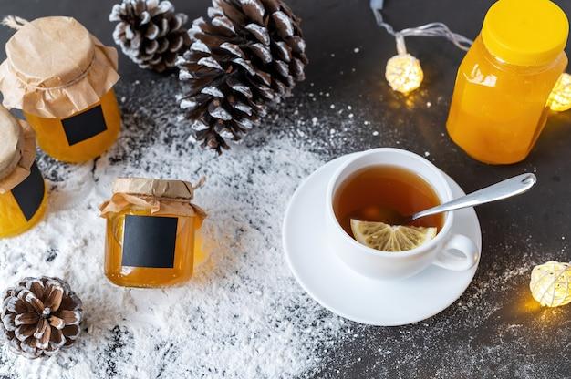 Skład produktów miodowych. miód w słoikach, szyszki herbaty i jodły.