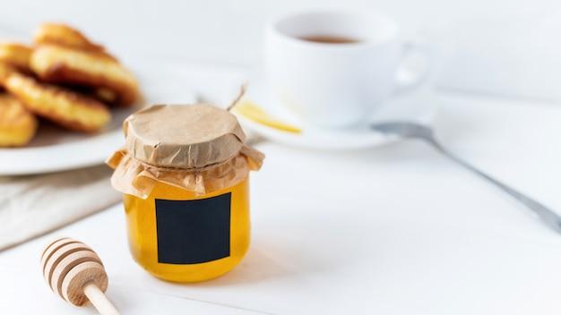 Skład produktów miodowych. miód w słoiku, obiad, herbata i specjalna łyżeczka. biała powierzchnia