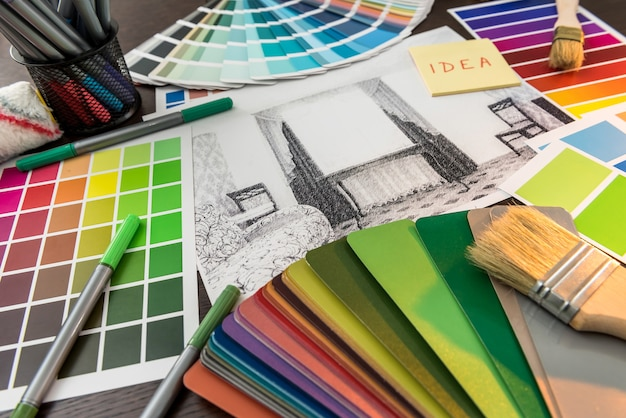 Skład projektu domu i pędzle z paletą kolorów na stole