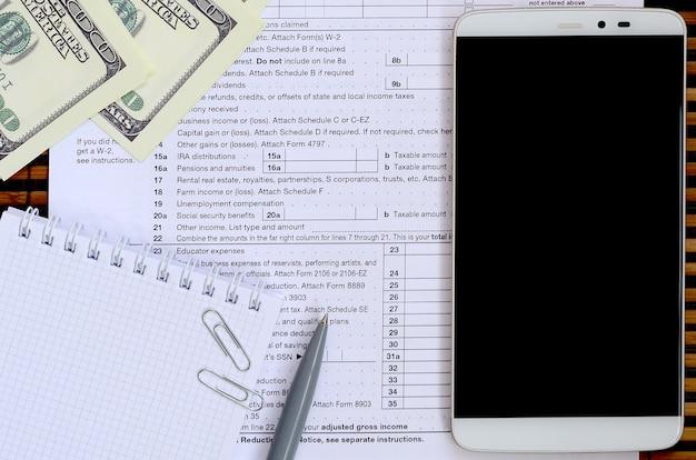 Skład przedmiotów leżących na formularzu podatkowym 1040. rachunki dolarowe, długopis, kalkulator, smartfon, spinacz do papieru i notatnik. czas płacić podatki
