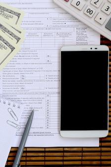 Skład przedmiotów leżących na formularzu podatkowym 1040. rachunki dolarowe, długopis, kalkulator, smartfon, spinacz do papieru i notatnik.