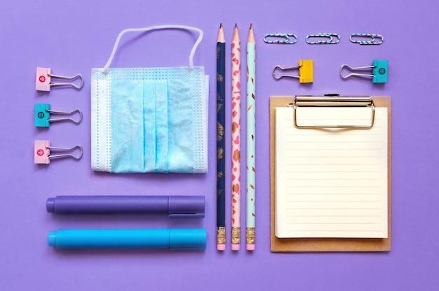 Skład przyborów szkolnych na fioletowym tle