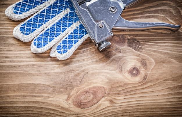 Skład rękawic ochronnych zszywacza pistoletu na drewnianej desce