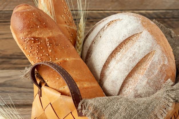 Skład różnych produktów pieczonych w koszu na tle rustykalnym. domowe świeże ciasto.