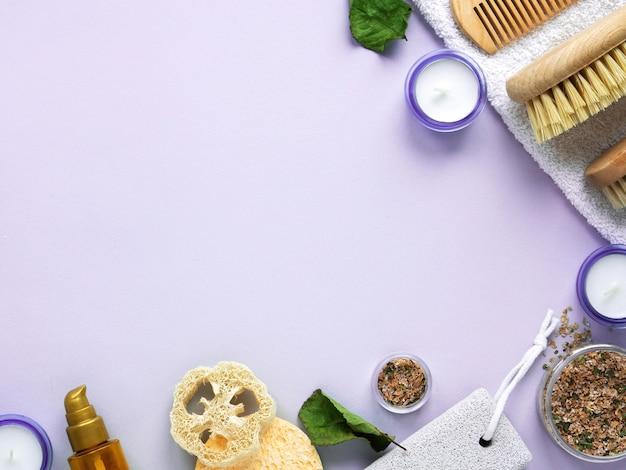 Skład rzeczy do samoopieki. gąbki, pędzle, kremy i świeczki na fioletowym tle