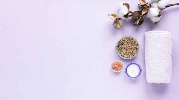 Skład rzeczy do samoopieki. sól, ręcznik, przyprawy i świece na fioletowym tle