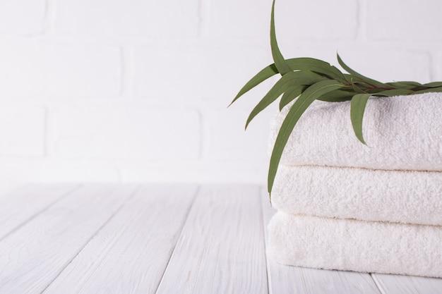 Skład spa na drewnianym stole. stos trzech białych puszystych ręczników kąpielowych z gałęzi eukaliptusa.