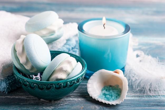 Skład spa z makaronikiem z bomby do kąpieli i suchymi kwiatami na rustykalnym tle. olejek eteryczny i sól. zabiegi kosmetyczne i relaksacyjne