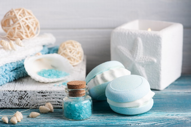 Skład spa z makaronikiem z bomby do kąpieli i suchymi kwiatami na rustykalnym tle. świece i sól. zabiegi kosmetyczne i relaksacyjne