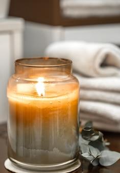 Skład spa z płonącą świecą, ręczniki kąpielowe z bliska. koncepcja aromaterapii.