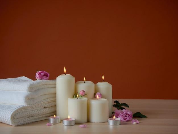 Skład spa z płonącymi świecami zapachowymi i różami na drewnianym stole